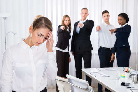 blaming: Businesspeople Blaming Frustrated Female Colleague In Office