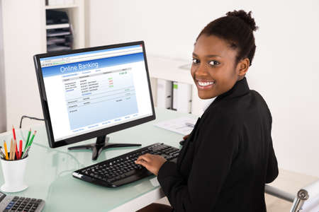 american money: Young Happy African Businesswoman Doing Online Banking On Computer At Office