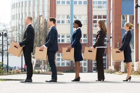 Groep multiraciale ondernemers met kartonnen dozen staan in een lijn