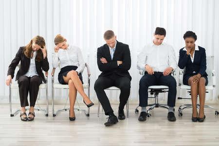 Empresarios en una silla durmiendo en una sala de espera Foto de archivo