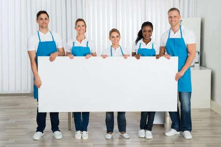 anuncio publicitario: Grupo de felices de limpieza en uniforme con la bandera en blanco en oficina
