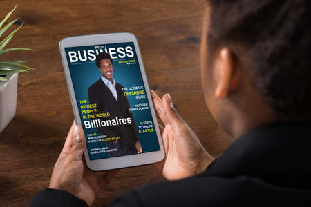 Primer plano de una mujer de negocios leyendo la revista en línea sobre la tableta digital en la Oficina Foto de archivo