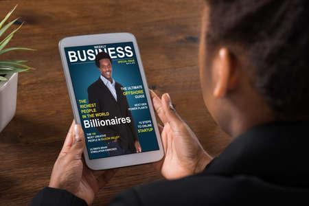Primer plano de una mujer de negocios leyendo la revista en línea sobre la tableta digital en la Oficina Foto de archivo - 56931363