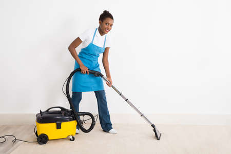 carpet stain: Young Happy Female Janitor Using Vacuum Cleaner On Floor At Office Stock Photo