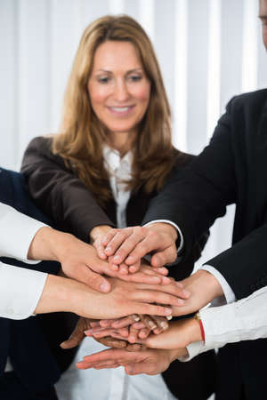 team hands: Group Of Businesspeople Together Putting Hands On Each Other Stock Photo
