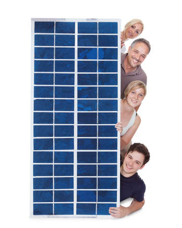 Happy Family Peeping Through Solar Panel Against White Background photo