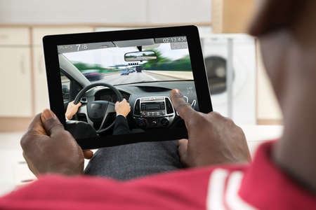 to and fro: Close-up Of Man Using Digital Tablet Fro Playing Car Game Stock Photo
