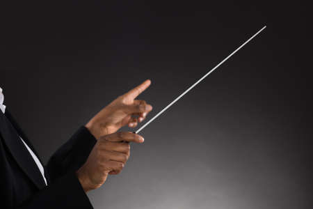 choral: Close-up Of Female Orchestra Conductor Holding Baton Over Black Background Stock Photo