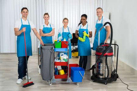 Groupe de Cleaners heureux debout avec des équipements de nettoyage Dans Office
