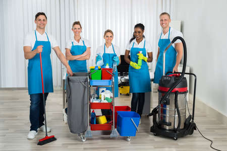 Groupe de nettoyeurs heureux debout avec des équipements de nettoyage au bureau