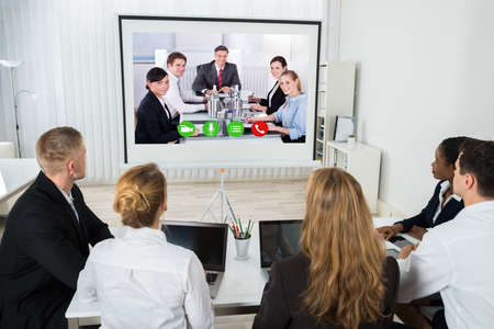 conference call: Group Of Businesspeople Together Videoconferencing At Workplace Stock Photo