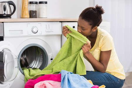 Mujer africana joven que huele la ropa después del lavado en casa Foto de archivo
