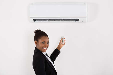 Young Happy Businesswoman Operating Air Conditioner With Remote Control In Office