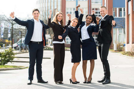 diverse: Group Of Happy Multi-racial Businesspeople Standing With Arm Raised In Front Building