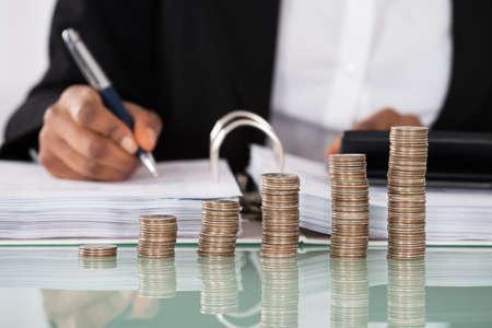 Primer plano de la empresaria del impuesto Cálculo con la pila de monedas en el escritorio Foto de archivo