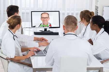 videoconferencing: Group Of Doctors Videoconferencing With Male Doctor On Computer In Hospital