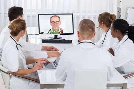 grupo de médicos: Grupo de médicos de videoconferencia Con doctor de sexo masculino en el ordenador en el Hospital