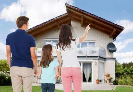 front house: Rear View Of A Family Standing In Front Of House Stock Photo