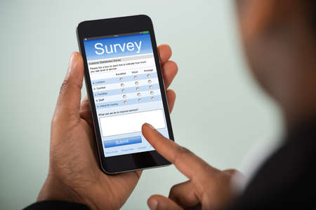 Close-up Of African Businesswoman Filling Online Survey On Mobile Phone Stockfoto