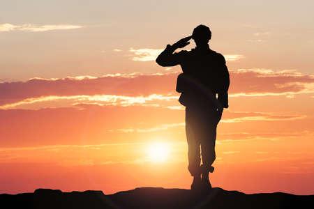 Sylwetka żołnierza salutowania podczas zachodu słońca