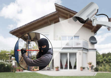 Surveillance Camera Capturing Burglar Using Crowbar To Open Glass Door Foto de archivo