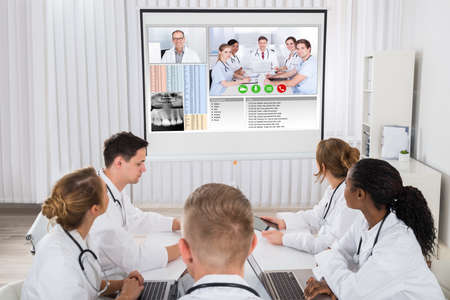 videoconferencing: Group Of Doctors Videoconferencing With Male Doctor In Hospital
