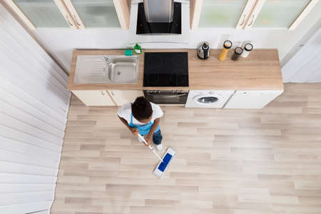 angle views: High Angle View Of Young Female Janitor Cleaning Floor In Kitchen