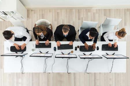 Hög vinkel tanke på Call Center operatörer som arbetar på datorer i Office