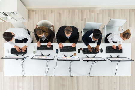 centro de computo: Vista de ángulo alto de Call Center operadores que trabajan en los equipos de oficina