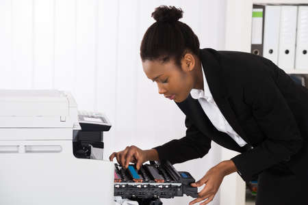 photocopier: Young Businesswoman Fixing Photocopy Machine In Office Stock Photo