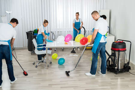 after party: Group Of Male And Female Janitors Cleaning The Office After Party