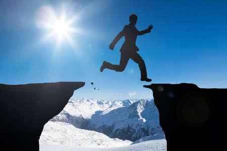 silueta hombre: Silueta del hombre que salta sobre las montañas contra Snowy Mountains