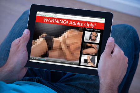 Close-up Of Man Watching Adult Movie On Digital Tablet Stock Photo