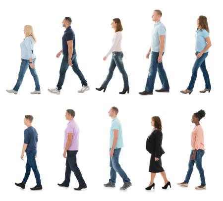 Menschengruppe in der Linie gegen weißen Hintergrund Gehen