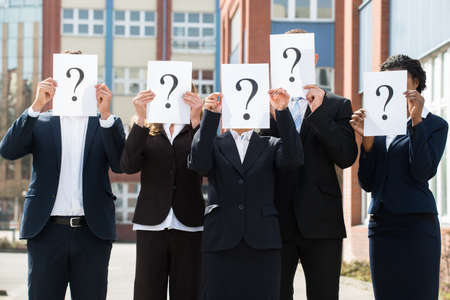 Grupo de empresarios que ocultan detrás de la cara de signo de interrogación sesión; al aire libre Foto de archivo