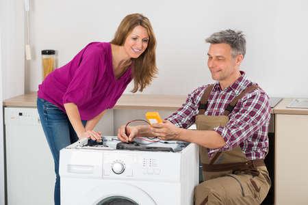 Mirando a la mujer Hombre Técnico Comprobación de lavadora en la cocina Foto de archivo