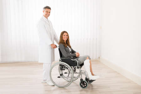 recovery: Male Doctor Assisting Happy Woman Sitting On Wheelchair Stock Photo