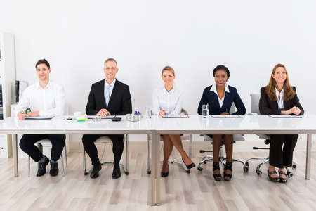 Happy Businesspeople Sitting At Conference With Graph On Desk Stockfoto