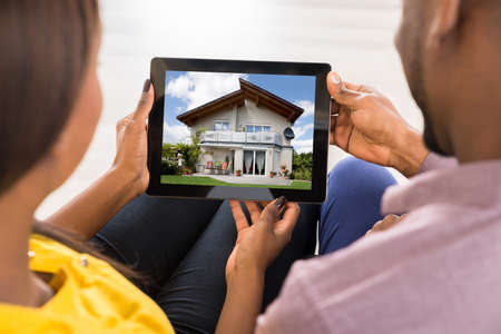 buying online: Close-up Of A Couple Looking At House On Digital Tablet