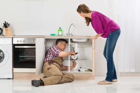 Male Plumber Repairing Pipe Under Sink While Woman Standing In Kitchen Stock Photo