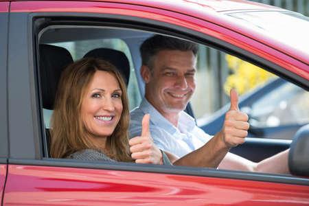 uomo rosso: Coppie mature felici seduto in auto nuova e mostrando thumbs up