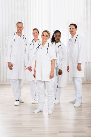 standing together: Group Of Happy Doctors With Stethoscope Standing In Hospital