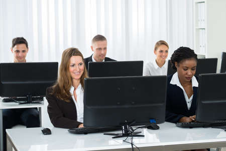 computers office: Happy Group Of Businesspeople Working On Computers In Office