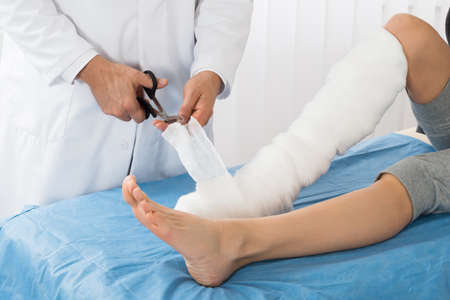 hospital patient: Doctor Bandaging Leg Of Patient In Hospital Stock Photo