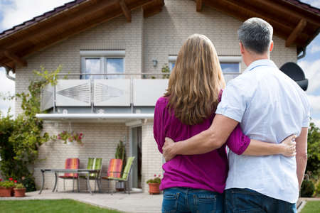 cute house: Rear View Of Couple Standing In Front Of Their House Stock Photo