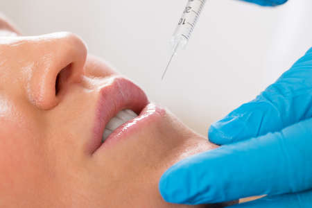 lips: Close-up Of Woman Receive Cosmetic Injection With Syringe On Lip