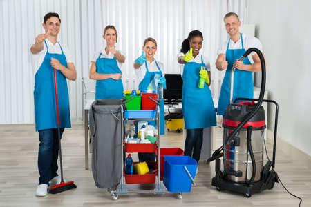 uniformes de oficina: Grupo de felices Limpiadores de pie con la limpieza de equipos en la oficina Foto de archivo