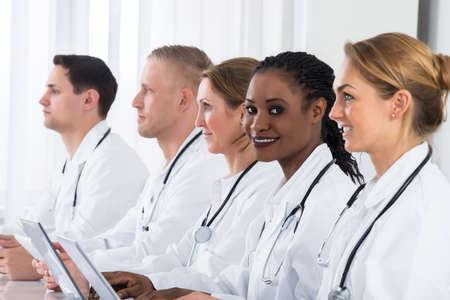 labcoat: Group Of Doctors In Labcoat Using Laptop At Desk Stock Photo