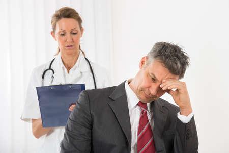 Médico con el portapapeles de pie detrás del de negocios que tiene dolor de cabeza en la Clínica