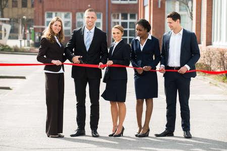 Businesspeople heureux à l'ouverture de coupe du ruban Avec Scissor
